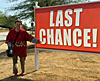 image of phil maggitti standing next to a sign that reads last chance