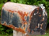 image of a beat up, rusty old mailbox